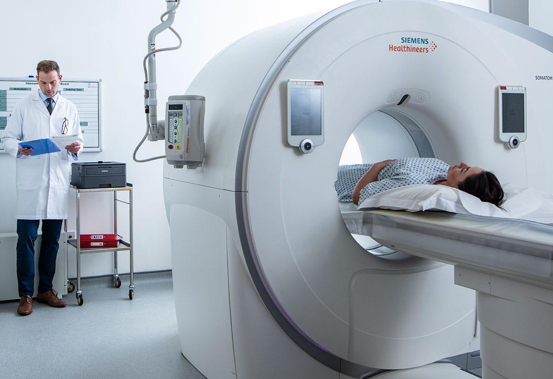 Kvinnelig pasient i CT-skanner en lege står ved siden aven  Brother HLL2370DW skriver