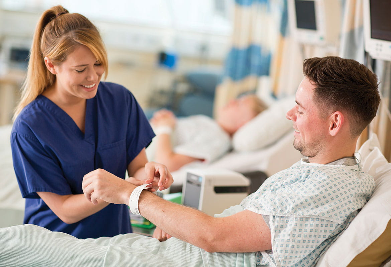 Sykepleier i blå uniform som fester et ID-armbånd på en pasient som ligger i en seng