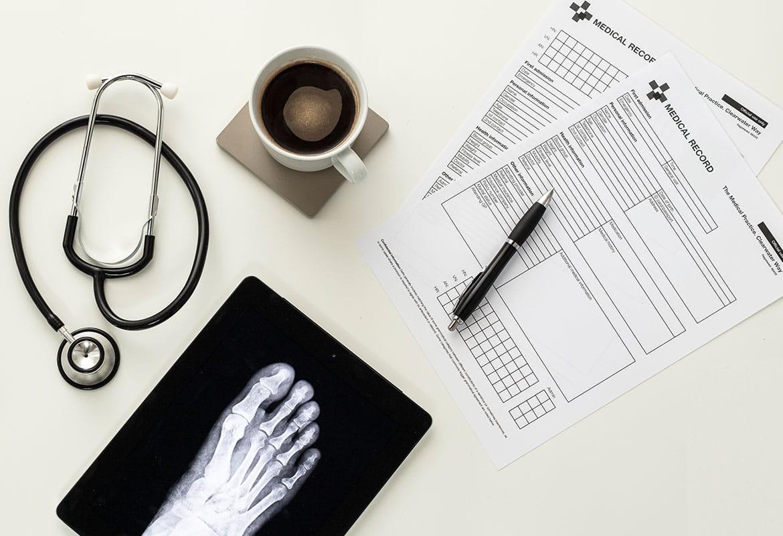 Medisinske skjema, penn, kopp kaffe, stetoskop, røntgenbilde av en fot på et hvitt bord