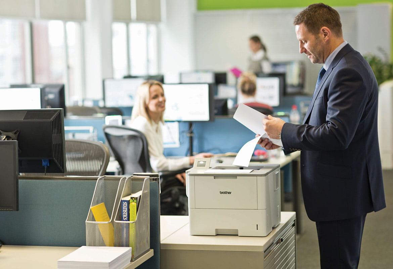 En mann med dokumenter i hånden står ved en Brother skriver i et kontorlandskap