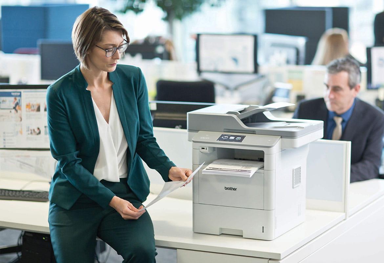 En kvinne med dokumenter i hånden ved en Brother skriver i et kontorlandskap