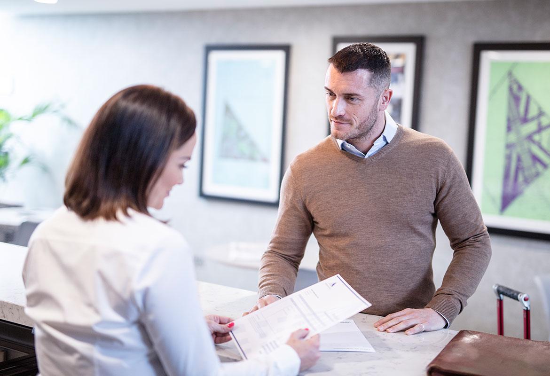 En kvinnelig resepsjonist snakker med en mannlig kunde