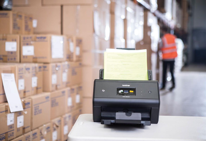 En Brother dokumentskanner med fraktdokumenter i dokumentmateren som står på et lager