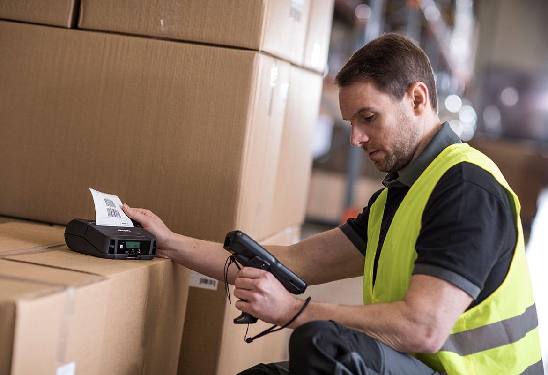En lagermedarbeider på et lager skriver ut en fraktetikett på en mobil etikettskriver fra Brother