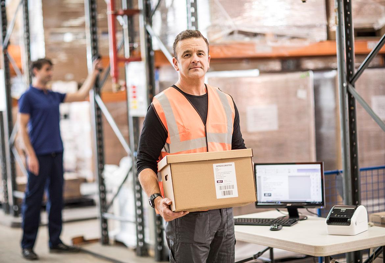 En lagermedarbeider på et lager bærer på en eske som er merket med en fraktetikett