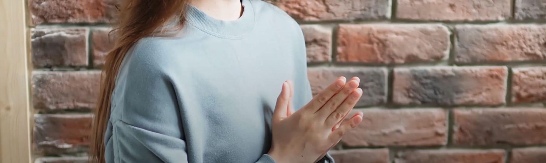 En kvinne sitter med hendene sammen