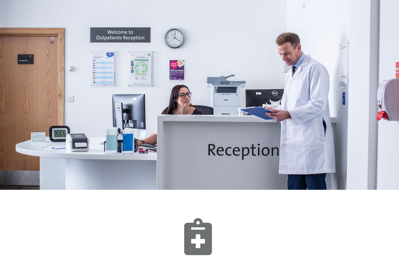 En lege står i en resepsjon og har en samtale med resepsjonisten