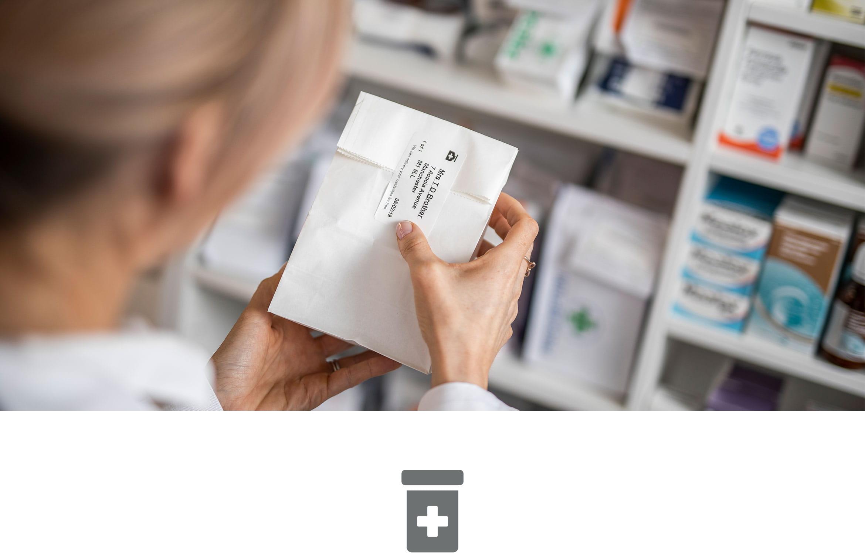 En farmasøyt holder en papirpose som er merket med en etikett