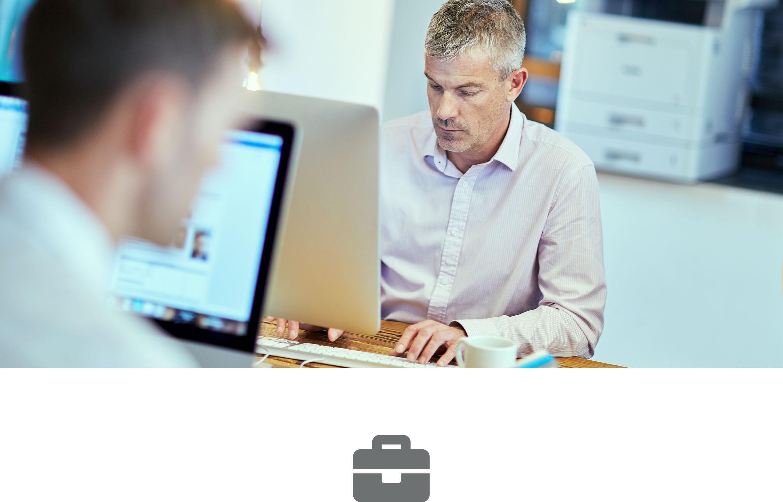 To menn jobber ved en datamaskiner på et kontor