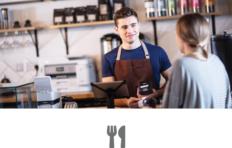 En ansatt i en kafe står bak disken og snakker med en kunde.  En Brother blekkskriver er plassert på en benk bak disken