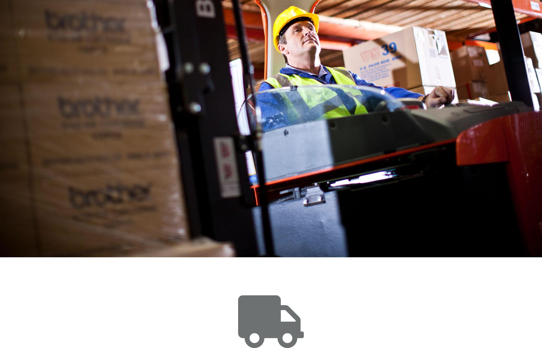 En lagermedarbeider med gul hjelmog vest jobber på et lager