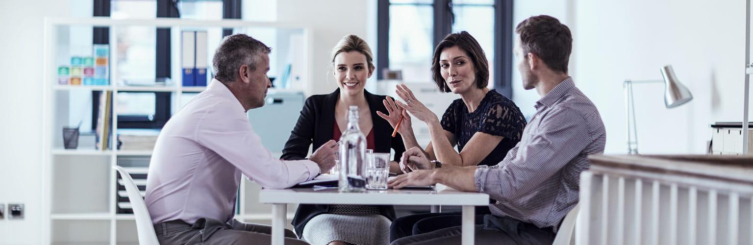 to menn og to damer rundt et bord på et kontor
