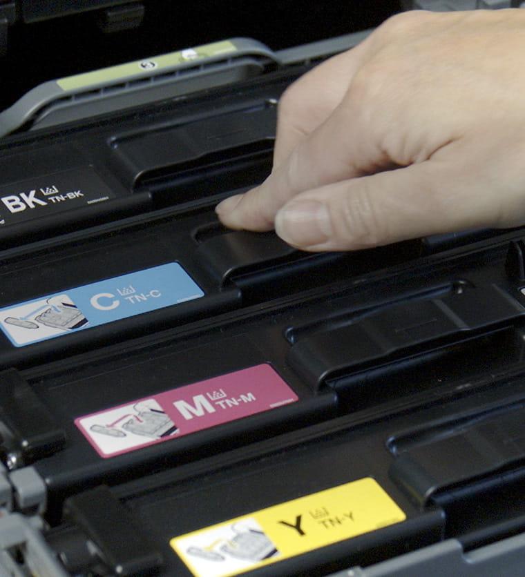 En person plasserer tonerkassetter i en printer