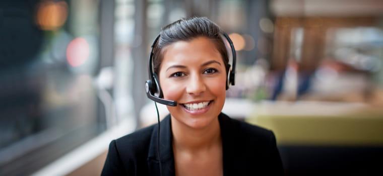 En kvinnelig supportmedarbeider med hodetelefoner