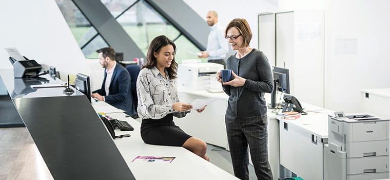 To kvinner snakker sammen ved en kontorpult