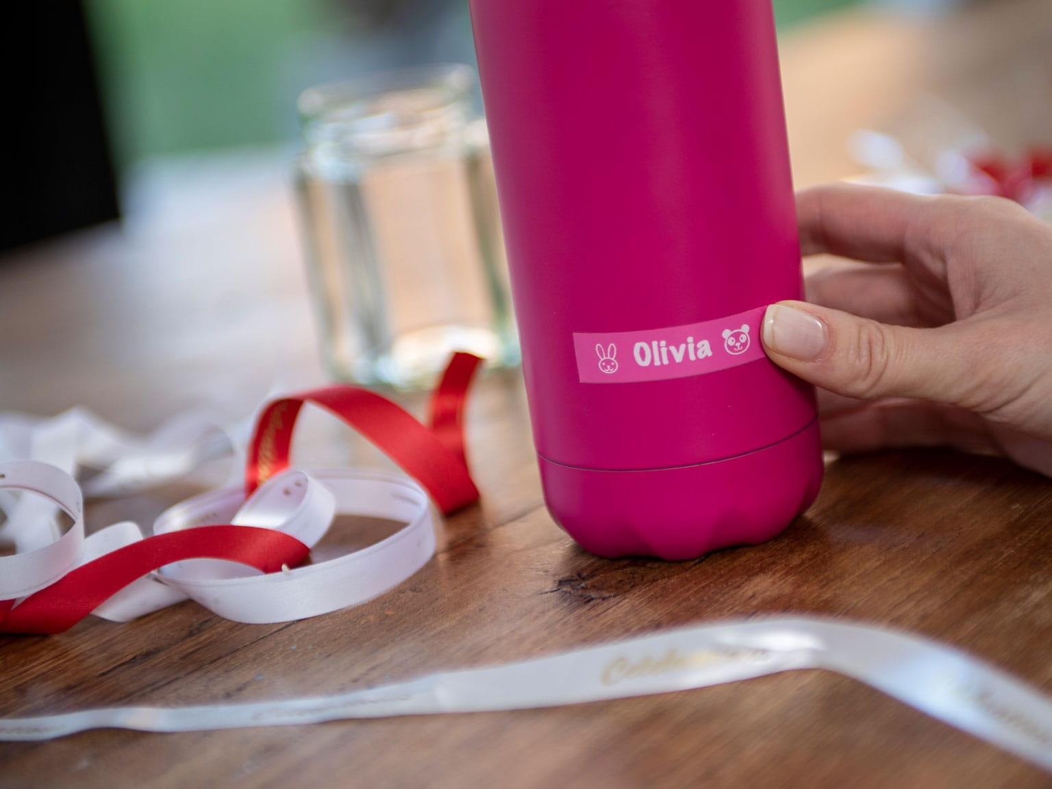 En person fester en Brother P-touch merkelapp med hvit skrift på rosa bunn på en rosa vannflaske