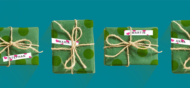 En rad med julegaver pakket inn i grønt papir merket med en hvit Brother P-touch merkelapp med rosa hjerter