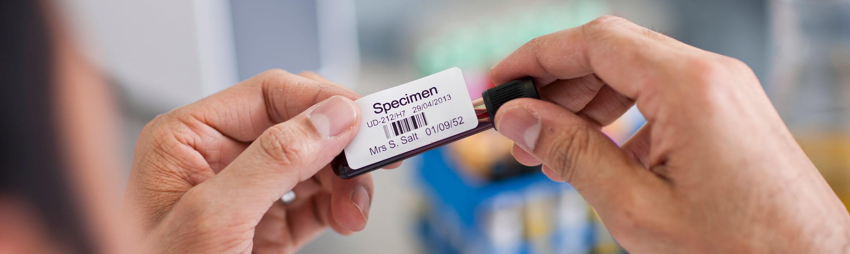 En etikett festes på et glass med blodprøve
