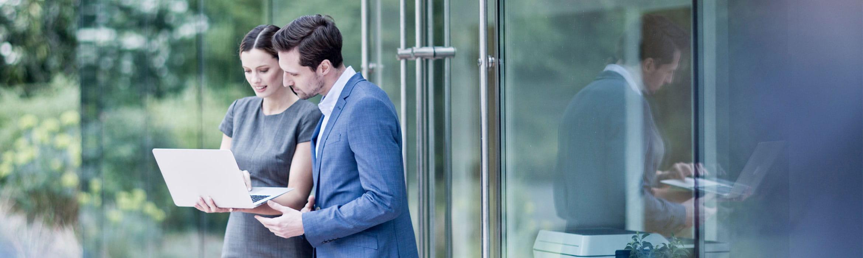 En mann og en kvinne står utenfor et kontor og ser på en en laptop