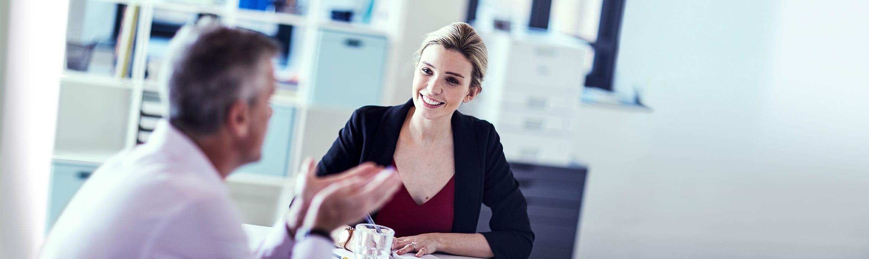 En mann og en kvinne i en samtale på et kontor