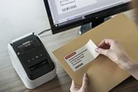 Etikett med sort og rød skrift som er skrevet ut på en Brother QL800 etikettskriver festes på en konvolutt