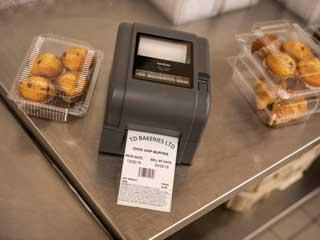En Brother etkettskriver i TD4T-serien plassert på en stålbenk med bakevarer i et bakeri
