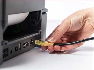 Ethernet-kabel kobles til den bakre porten til en Brother etikettskriver i TD4T-serien