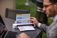 En mann skanner et A4 dokument i farger på en Brother DS740D mobil skanner