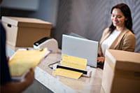 En kvinnelig resepsjonisti med bærbar datamaskin scanner et dokument på en Brother DS740D mobil skanner