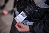 En person i uniform bærer en mobil 2 tommers RJ mobil skriver i en skulderstropp mens han skriver ut