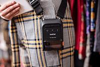 En person bærer en 2 tommers RJ mobil skriver som er i en skulderstropp