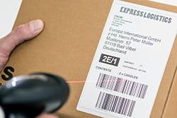 En pakke med DK leveranseetikett med strekkode skannes