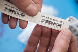 En hånd holder etiketter med strekkoder i fast format