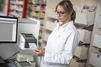 En kvinne skriver ut medisinske etiketter fra en Brother etikettskriver i TD4-D-serien