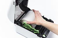 En hånd plasserer en etikettrull i en Brother etikettmaskin i TD4D-serien
