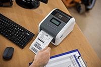 En Brother TD4550DNWB etikettskriver på et skrivebord med utskrift av en etikett med strekkoder