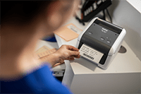 En sykepleier skriver ut pasient etikett ved hjelp av Brother TD4410D etikettskriver