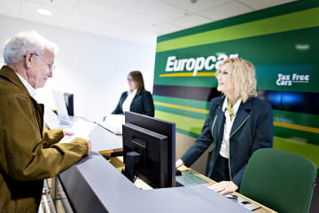 En kunde i samtale med en ansatt ved en skranke i Europcar
