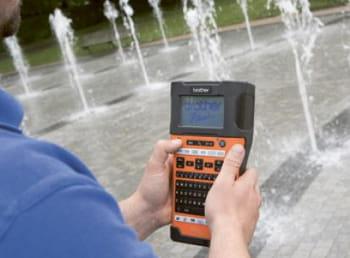 En mann holder en P-touch merkemaskin i hånden og en vannfontene er i bakgrunnen
