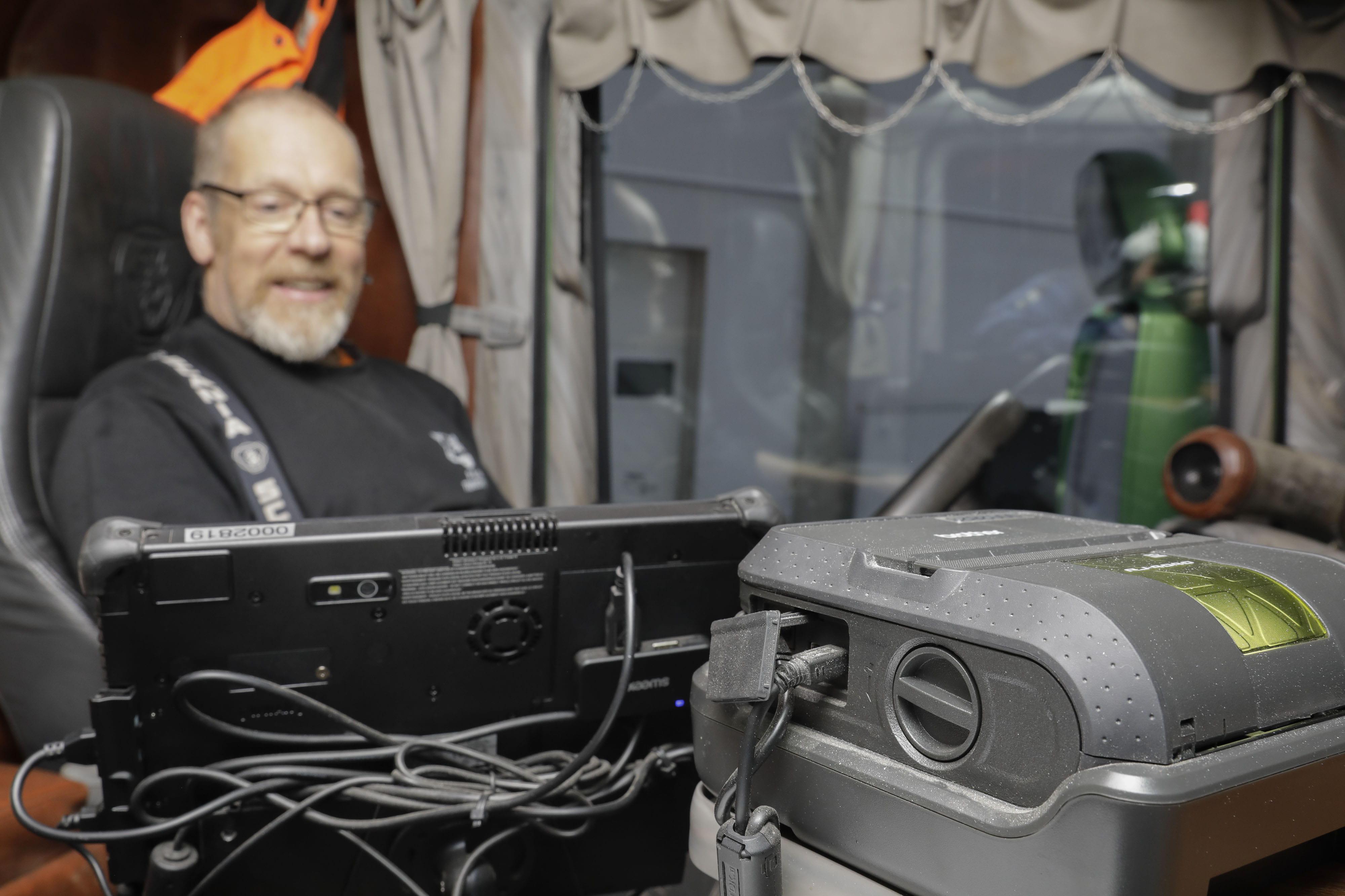 Sjåfør i lastebil med Brother kvitteringsskriver på dashborard