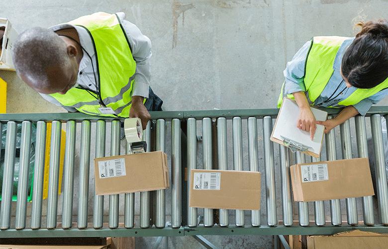 To ansatte ved et samlebånd med pakker som merkes og registreres