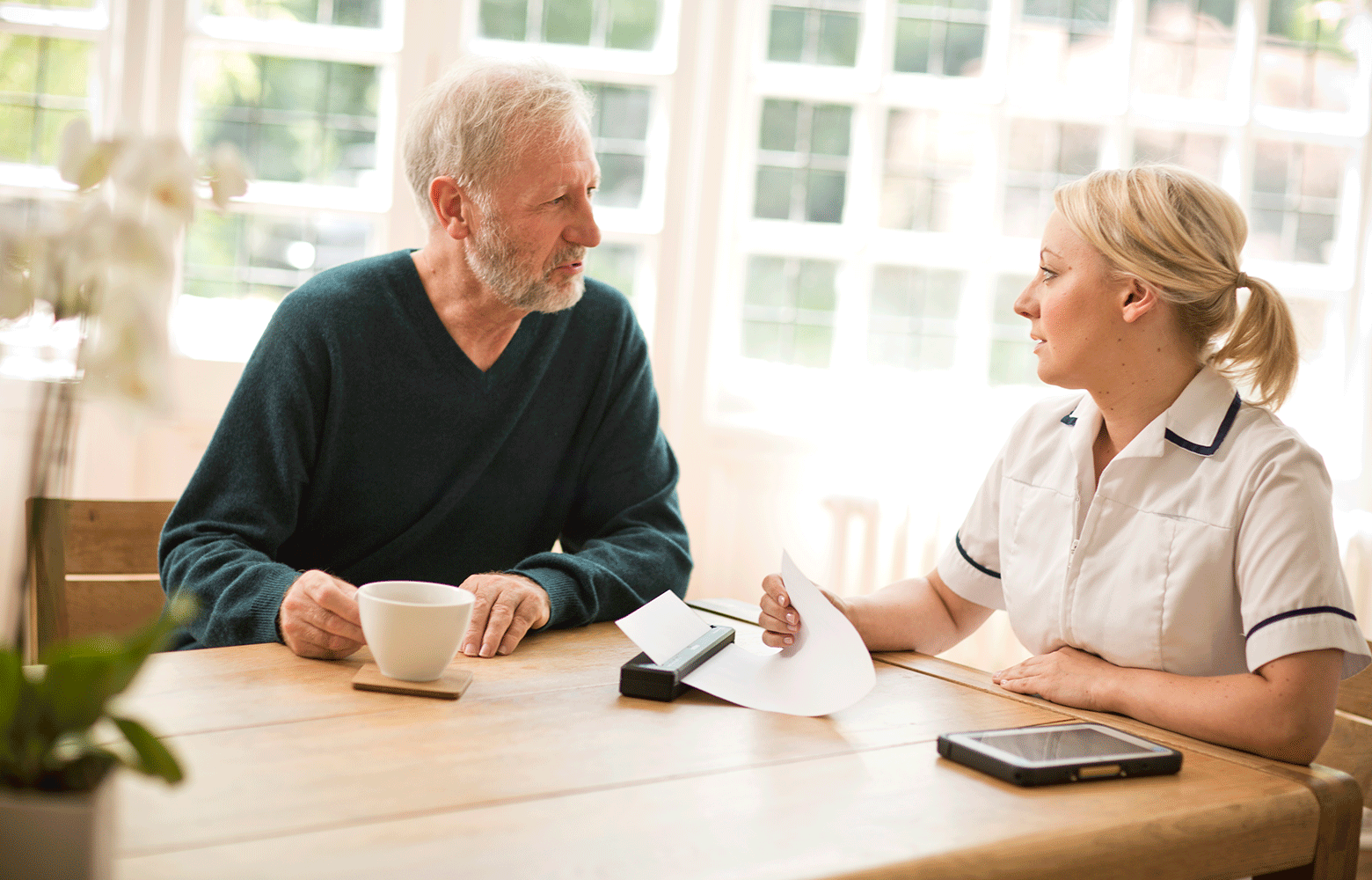 En helsearbeider sitter ved et bord i samtale med en pasient og skriver ut et dokument på en Brother mobil skriver i PJ-serien