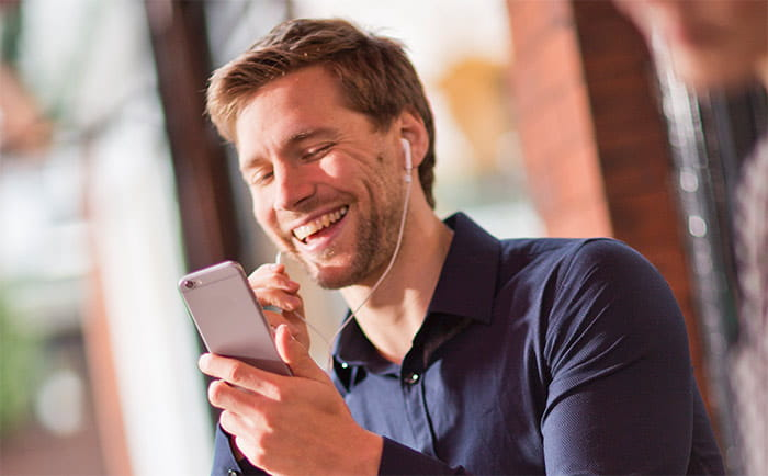 Brother OmniJoin man outside on mobile having conversation over headphones